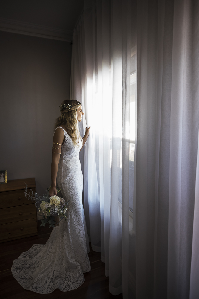 The bride getting ready by the window