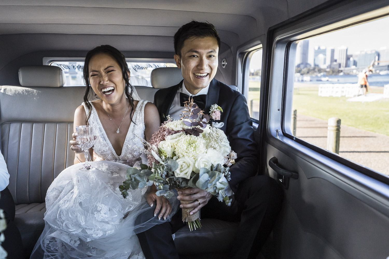 Bride and groom in back of the limo